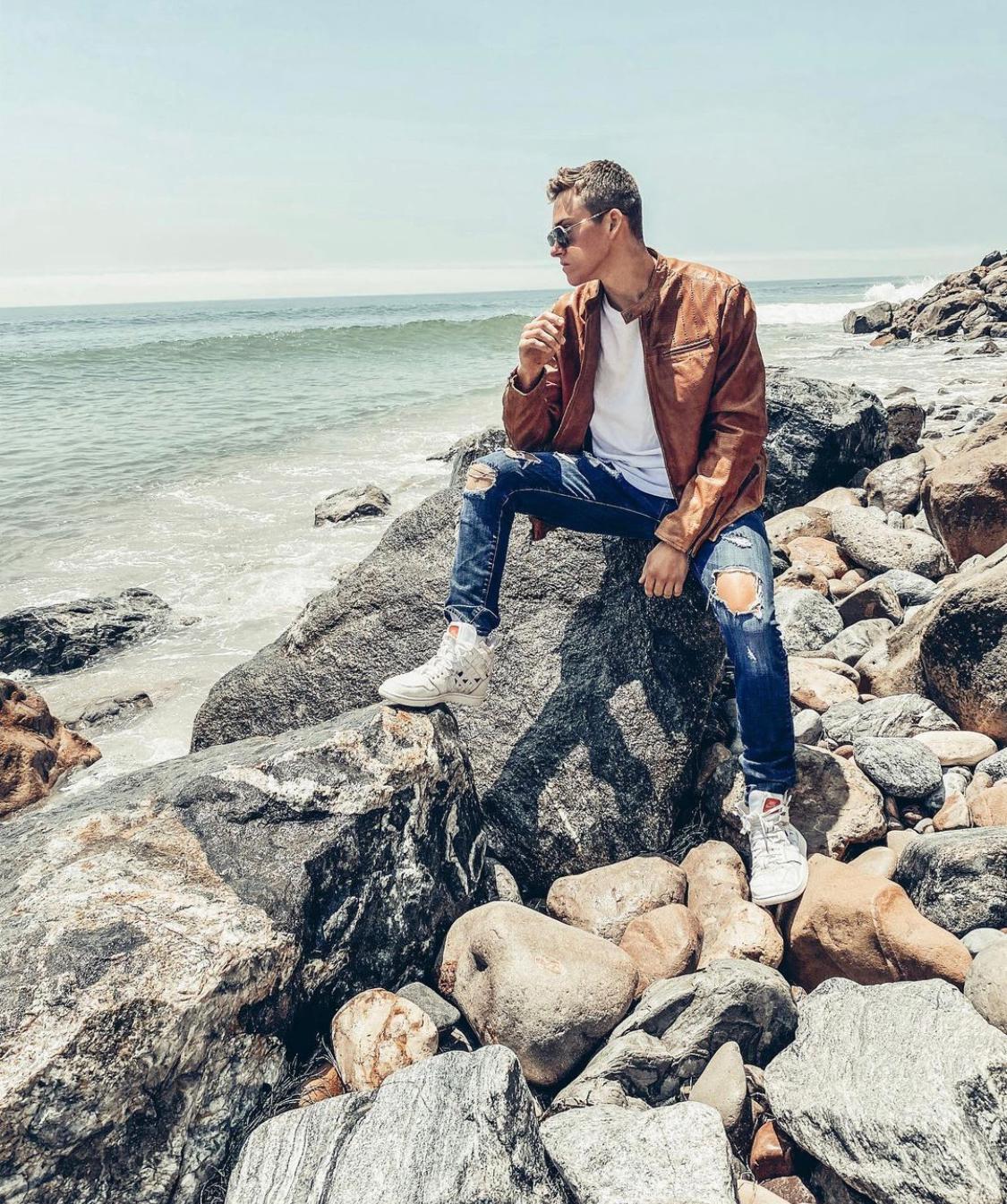 Truitt Battin rocking a John Varvatos jacket as he relaxes by the beach